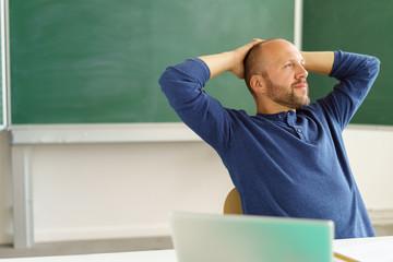 entspannter lehrer verschränkt die arme hinter dem kopf