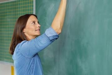 lehrerin schreibt im unterricht etwas an die schultafel