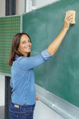 lehrerin wischt die tafel im klassenzimmer