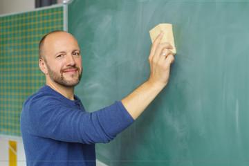 lehrer wischt die tafel im klassenzimmer