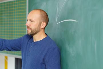 lehrer steht an der tafel und deutet mit der hand nach vorne in die klasse