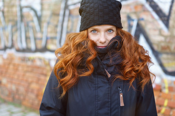 frau mit mütze und winterjacke steht draußen in der stadt