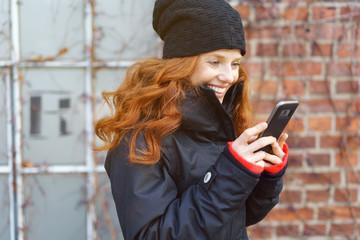 frau ist im winter in der stadt unterwegs und schaut auf ihr mobiltelefon