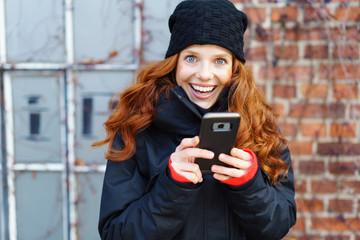 lachende frau steht draußen mit ihrem mobiltelefon