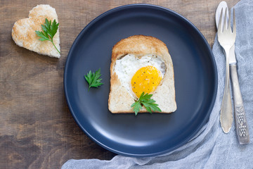 Egg in a heart-shaped bread with parsley, romantic breakfast.