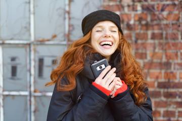 glückliche frau hält ihr mobiltelefon in beiden händen und lacht