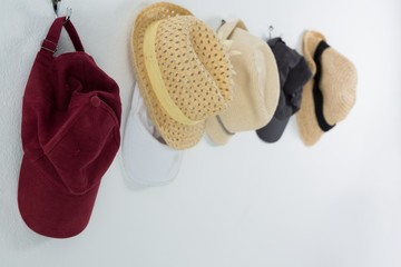 Various straw hats and caps hanging on hook