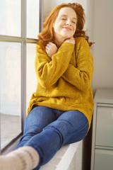 frau sitzt am fenster und kuschelt sich in ihren warmen pullover