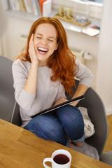 frau sitzt entspannt zuhause und lacht über lustige videos auf ihrem tablet-pc