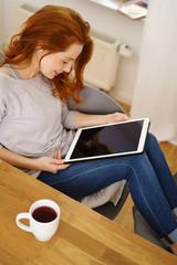 entspannte frau schaut auf ihr tablet