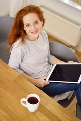 frau sitzt entspannt zuhause am tisch und liest am tablet-pc