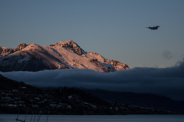 Sunrise on a snow capped mountain with fog in the valley.