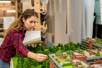 Young woman with blueprint looking at one of modern architectural constructions on city layout model