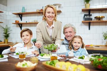 Hospitable grandparents and their grandchildren having breakfast in the kitchen