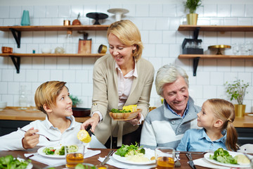 Grandmother giving boiled corn to her grandson by breakfast with mature man and little girl near by