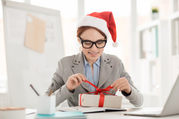 Smiling young impatient employee untying red ribbon on top of package with xmas gift