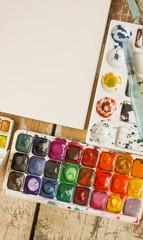 Watercolor paints, palette and paper