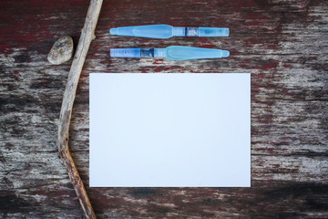 White paper sheet and water brushes on wooden background.