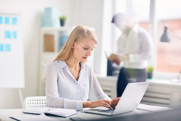 Young businesswoman typing on laptop keypad in office environment