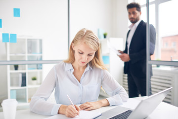 Busy young woman making notes in notebook on background of male employee