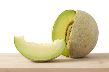 Japanese green melon slice and half on wooden cutting board