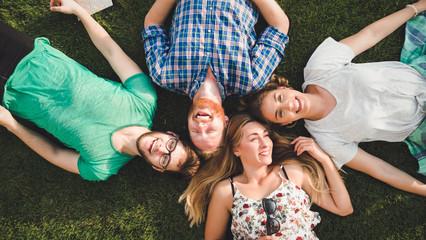 Happy joyful students lying in grass