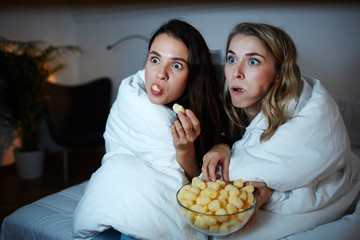 Curious girls eating corn rolls from bowl while watching captivating movie at night