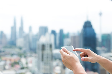 man's hand with mobile phone in modern city