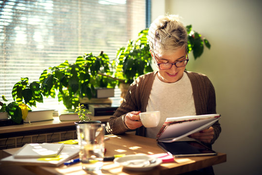 Charming cheerful satisfied middle age short hair woman sitting at the table in the morning at home and drinking a coffee while reading students tests or business statistics.
