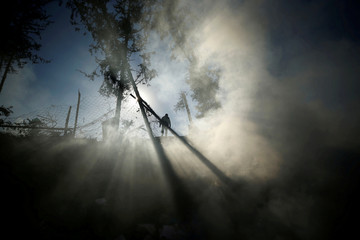 Smoke is seen as a Palestinian man inspects a militant target that was hit in an Israeli airstrike in the northern Gaza Strip