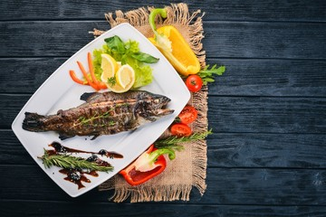Fish Trout baked with vegetables and spices. On a wooden background. Top view. Free space for text.