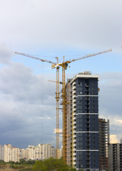 tower crane against the blue sky, the process of building a multi-storey building