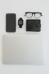 Various gadgets, spectacles and wallet on white background