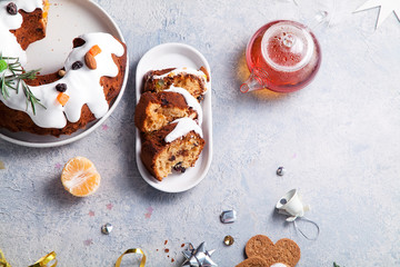 Slices of traditional christmas cake with dried fruits soaked in rum and sugar glaze. Teatime with heart-shaped ginger cookies. Christmas background with festive decoration. Copy space.