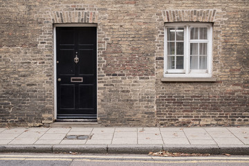 Black front door on a restored brick wall of a Victorian house residential building with white...