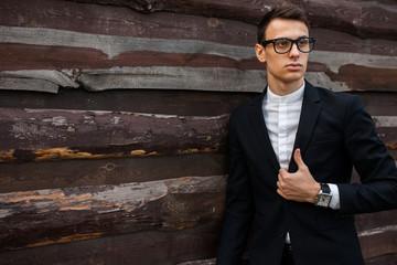 Stylish, beautiful, man in classic costume , posing near wooden wall.