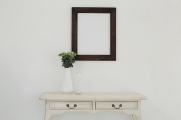Wooden frame and vase against white wall