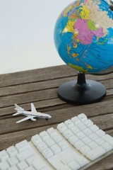 Globe, airplane model and keyboard on wooden plank