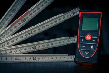 Laser ruler and folding ruler lying on the table waiting for measurements