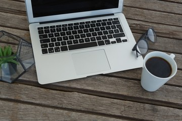 Laptop, spectacles, black coffee and pot plant on wooden plank