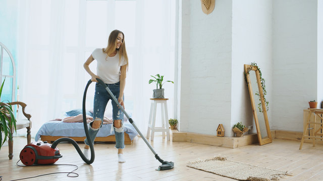 Young woman having fun cleaning house with vacuum cleaner dancing and singing at home