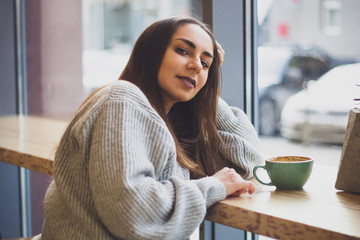 portrait of young beautiful smiling brunette girl in grey sweater drinking coffee at a table in  cafe