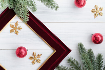 Top view of blank red picture frame with red decoration ball, gold snowflake , pine brance on white wood table top,Flat lay luxury holiday celebration still life,mock up for adding text,copy space