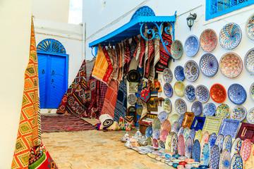 Souvenir earthenware and carpets in tunisian market.