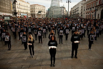 Animal rights activists from Igualdad Animal (Animal Equality) hold up pictures of animals they say are mistreated, during a demonstration to protest treatment of animals and draw attention to International Animal Rights Day, in Madrid