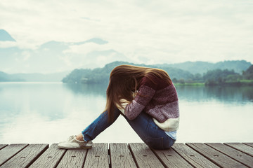 Depressed and stressed woman sitting on wooden pier