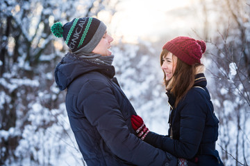 Young beautiful couple having fun in the snow covered forest park. New Year and winter clothes concept