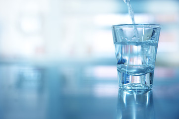 single glass shot with movement water for drinking in blue background