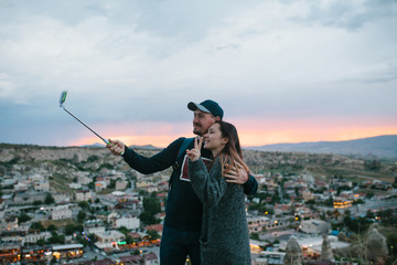 A beautiful couple doing selfie at sunset against the backdrop of the city of Goreme in Cappadocia in Turkey.