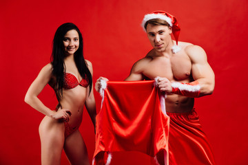 Christmas sports couple. sexy strong Santa Claus wars hat and costume with bikini girl.